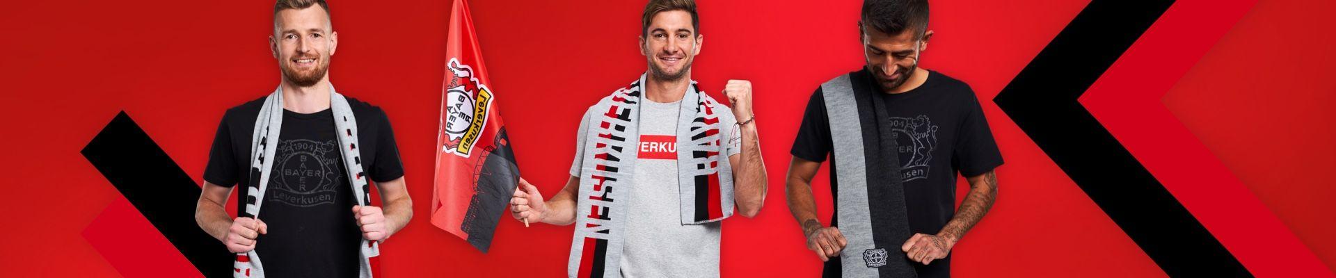 Lukas Hradecky posiert im T-Shirt Black und trägt einen Schal um den Hals. Lucas Alario trägt das T-Shirt Leverkusen, hält eine Fahne in der Hand und trägt einen Schal um den Hals. Kerem Demirbay trägt das T-Shirt Black und einen Schal über die Schulter.