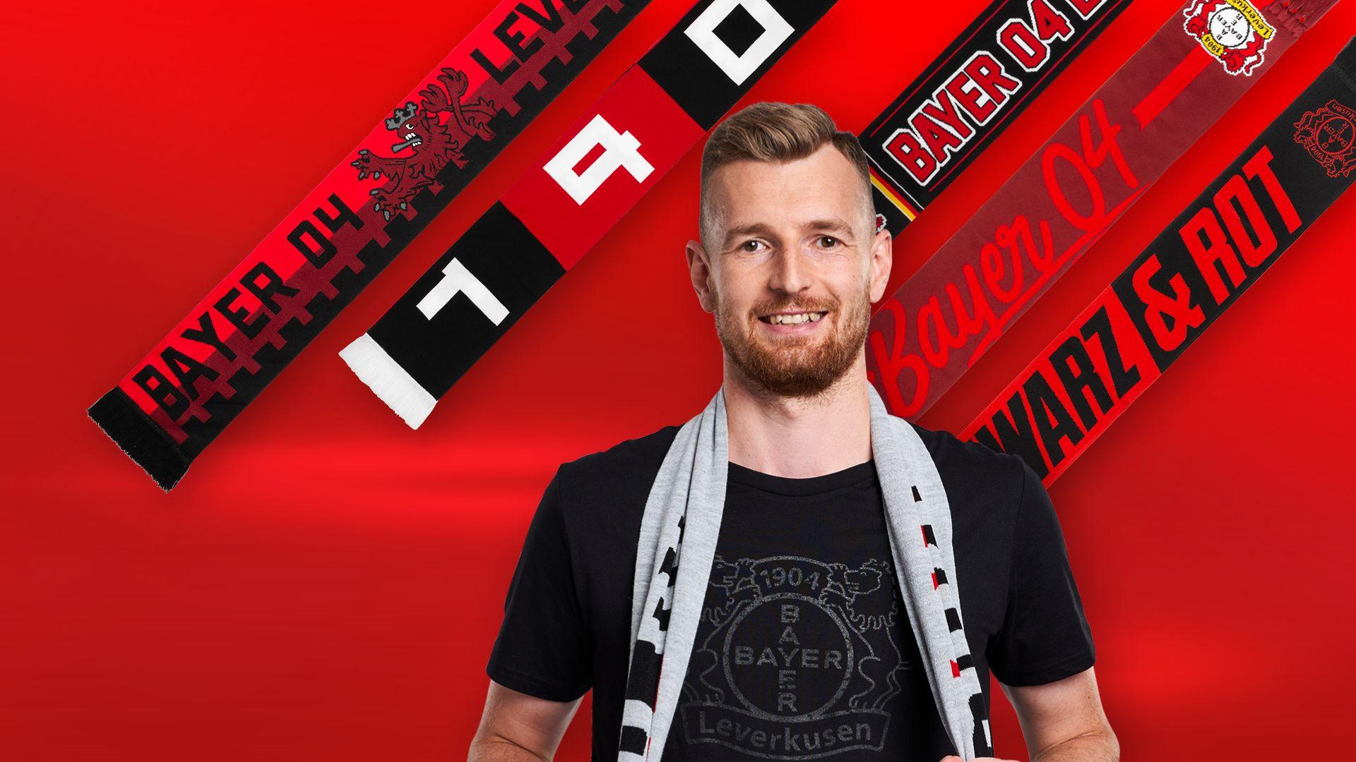 Im Vordergrund Lukas Hradecky mit einem umgehängten Fanschal. Im Hintergrund fünf Fanschals.