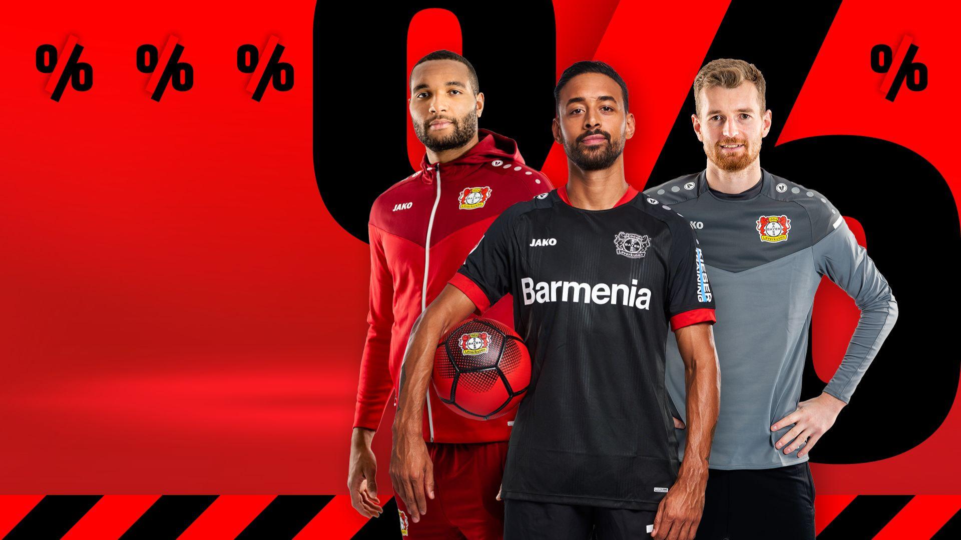 Jonathan Tah, Lukas Hradecky und Karim Bellarabi im Vordergrund. Bellarabi hält einen Fußball unterm Arm. Roter Hintergrund mit schwarzen Prozent-Zeichen.