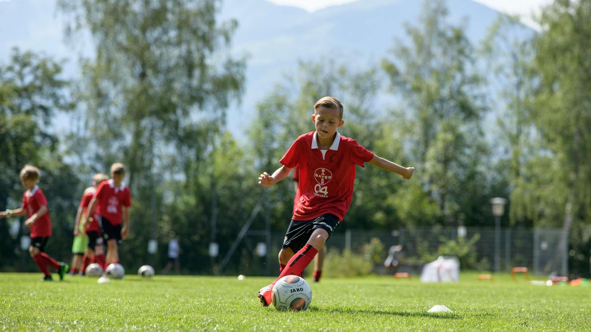 Ein Junge trägt das 40 Jahre Bundesliga Jubiläumstrikot und dribbelt mit Ball durch einen Hütchen-Parkour.